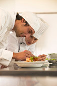 Female chef and male cook placing garnish on dishes, smiling