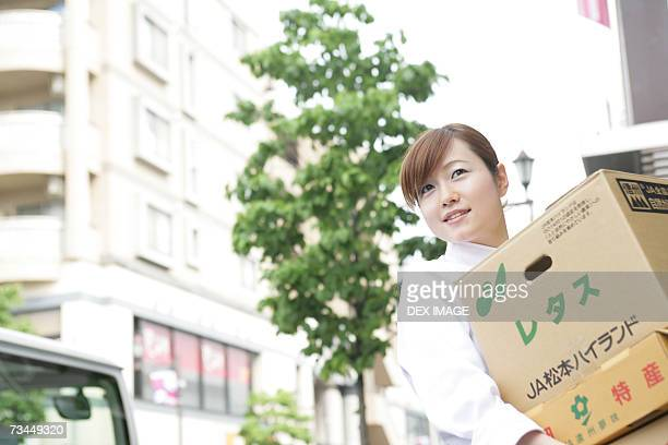 Female chef carrying cardboard boxes