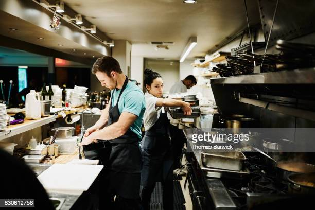 Female chef carrying pans through crowded kitchen preparing for dinner service in restaurant