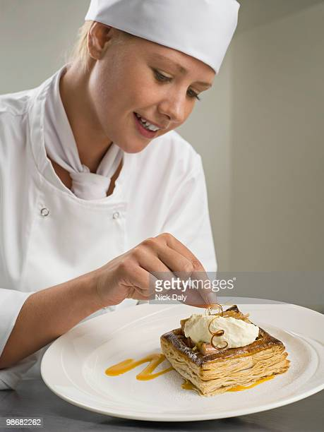 A female chef finishing a desert