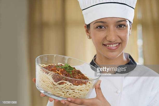 Female chef holding a bowl of spaghetti with Bolognese sauce
