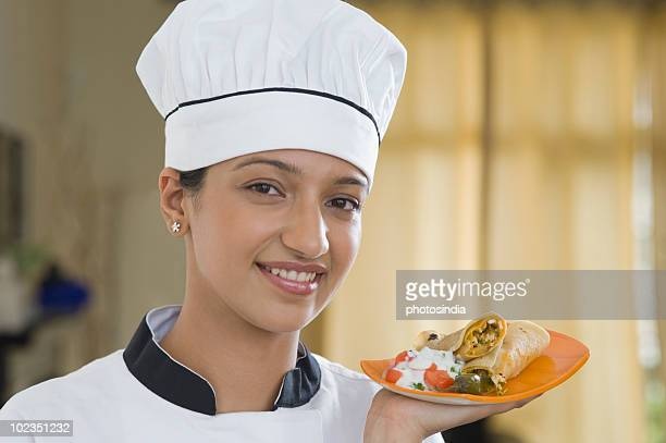 Female chef holding a plate of fajita and smiling