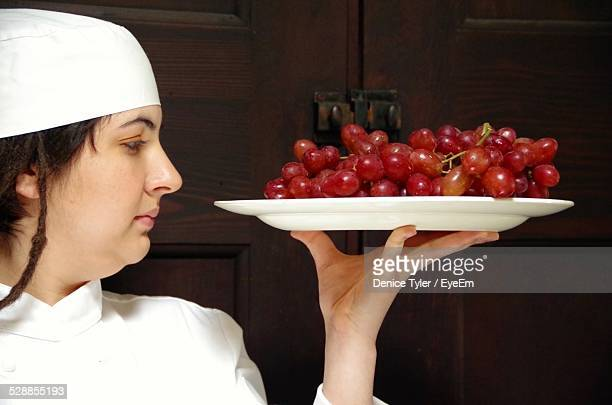 Female Chef Holding Fresh Red Grapes In Plate