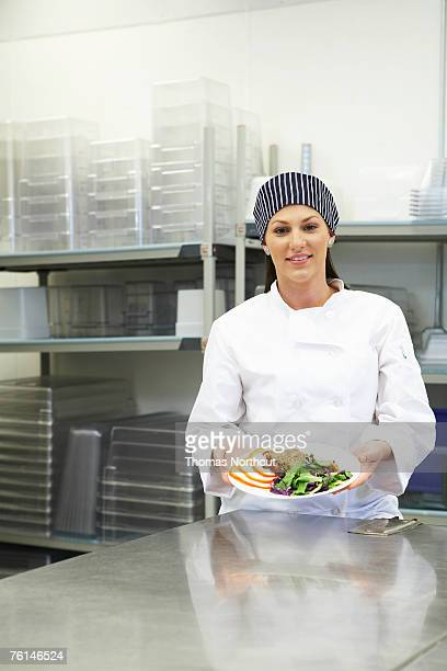 Female chef holding meal in kitchen, portrait