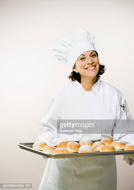 Female chef holding tray of baked rolls