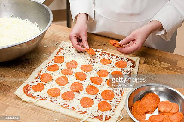Female chef making pizza in commercial kitchen