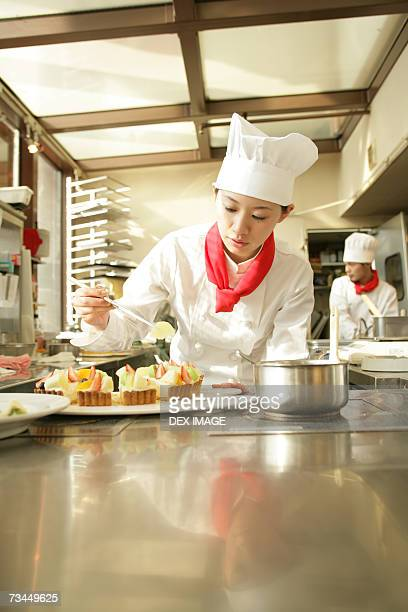 Female chef preparing a strawberry tart in a restaurant with a chef standing in the background