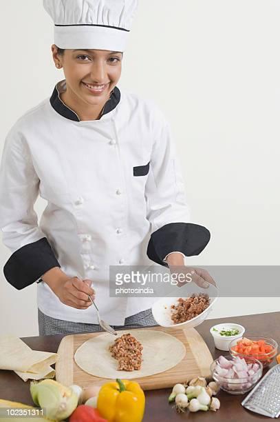 Female chef preparing fajita in the kitchen