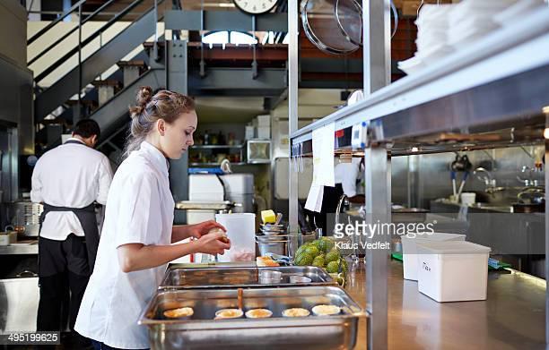 Female chef preparing food at restaurant
