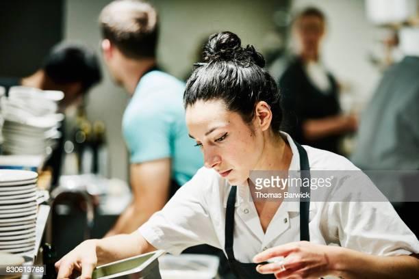 Female chef preparing for dinner in restaurant kitchen