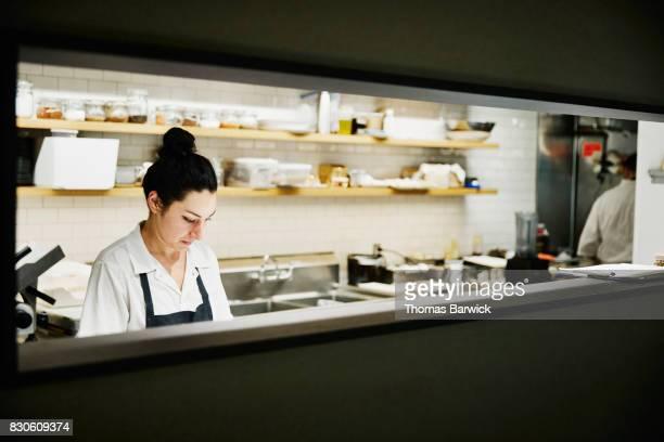 Female chef preparing for dinner service in restaurant kitchen