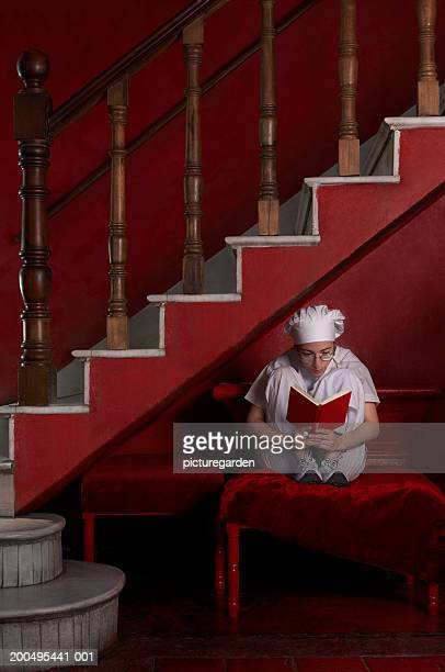 Female chef reading book beneath stairs