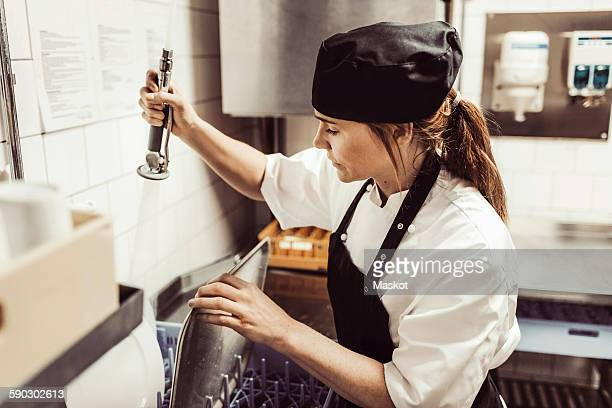 Female chef spraying water on plates in commercial kitchen