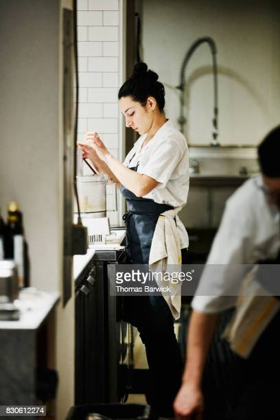Female chef using food processor in restaurant kitchen to prepare for evening meal service