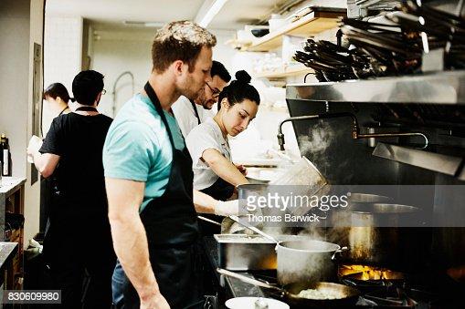 Restaurant Kitchen Staff kitchen staff working at stove in restaurant kitchen preparing for