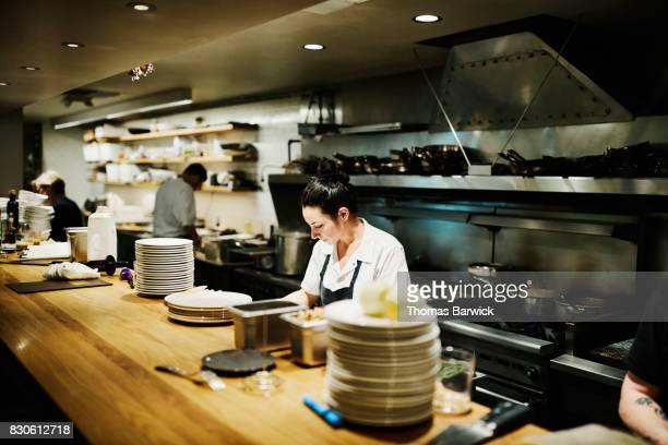 Female chef working in restaurant kitchen preparing for dinner service