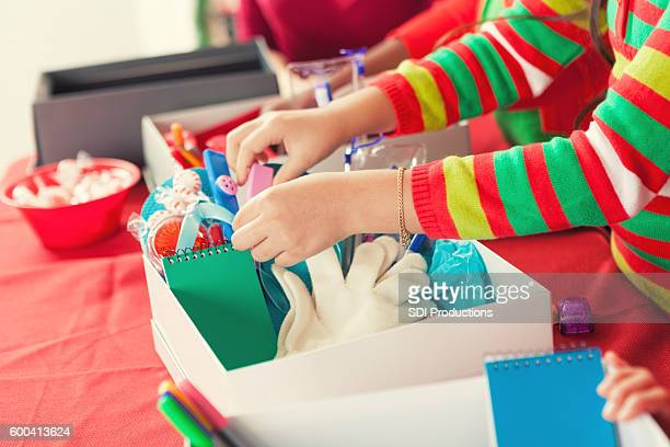 Female child filling Christmas donation boxes for children in need