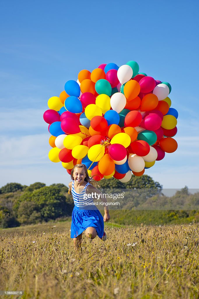 female child running with balloons : Stock Photo