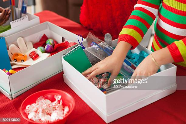 Female children filling holiday donation boxes for children in need