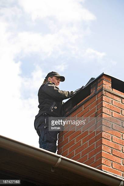 Female chimney sweeper on the roof cleaning a brich chimney.