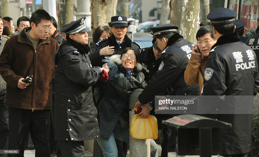 A female Chinese demonstrator is detained by police after protesting outside the site of the 13th Shanghai Municipal People Congress in Shanghai, 24 January 2008. The protests are usually over land and housing issues and regularly take place during the annual meeting of the Shanghai legislature, which meets to chart the political and economic course of China's main financial centre. AFP PHOTO/Mark RALSTON
