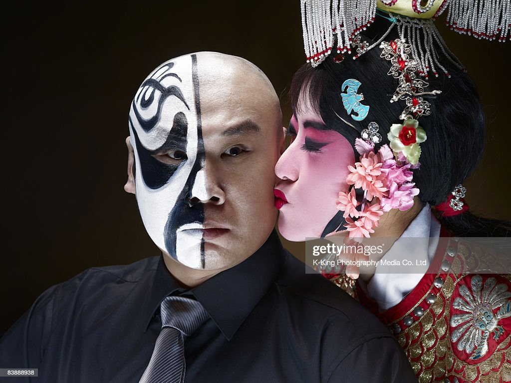 Female Chinese opera singer kissing male actor  : Stock Photo