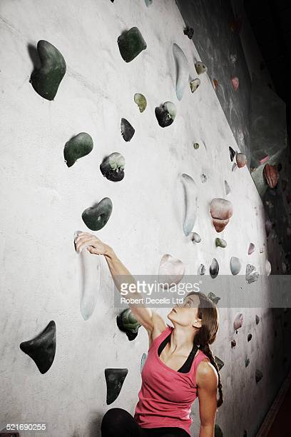 Female climber climbing indoor wall