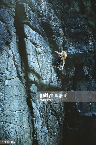 Weibliche Kletterer klammert sich an einer Klippe.