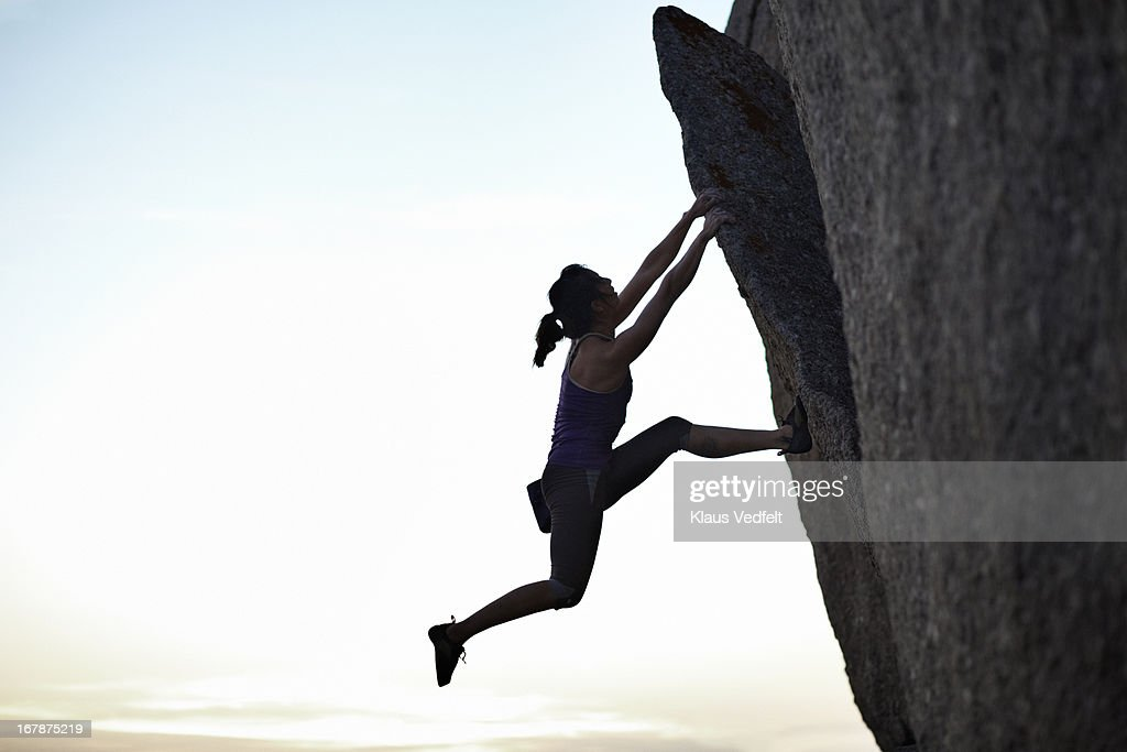 Female climber hanging in rock in the sunset