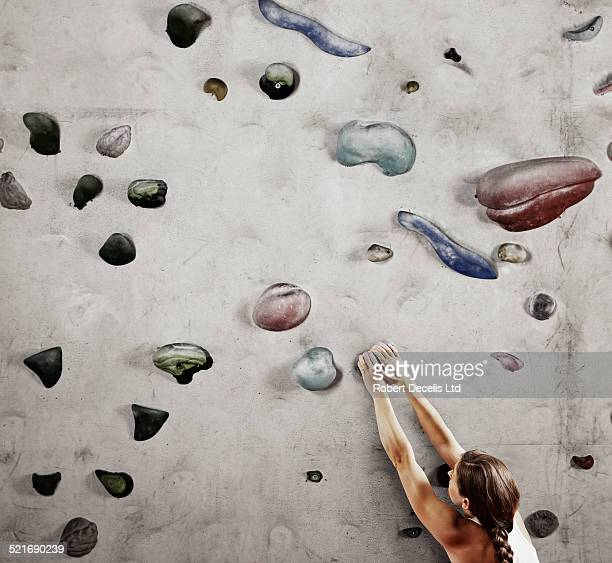 Female climber holding onto climbing wall