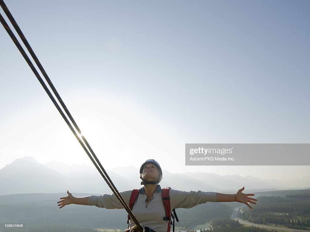 Female climber leans on rope above mtns, arms out