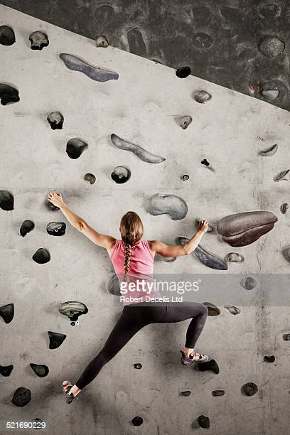 Female climber scaling indoor wall