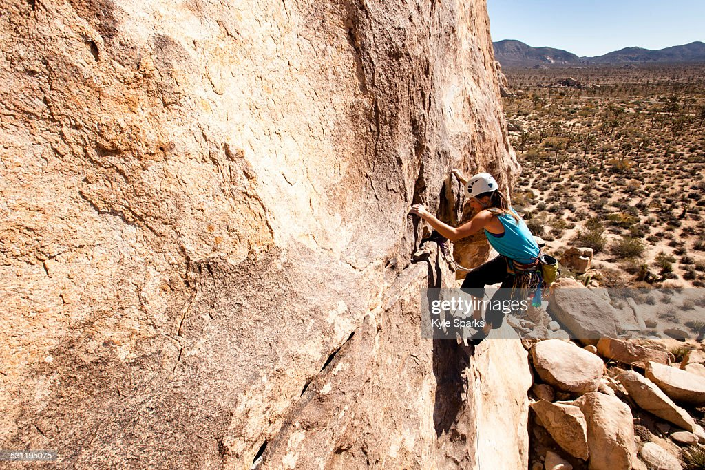 A female climber works her way up Sidewinder (5.10b) in Joshua Tree National Park, California.
