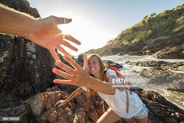 Female climbs on cliff, partner pulls out hand for assistance