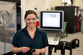 A smiling young female CNC machinist holding a cutting tool in front of a milling machine wearing safety glasses.