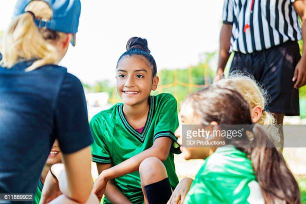 Female coach gives pep talk to her team