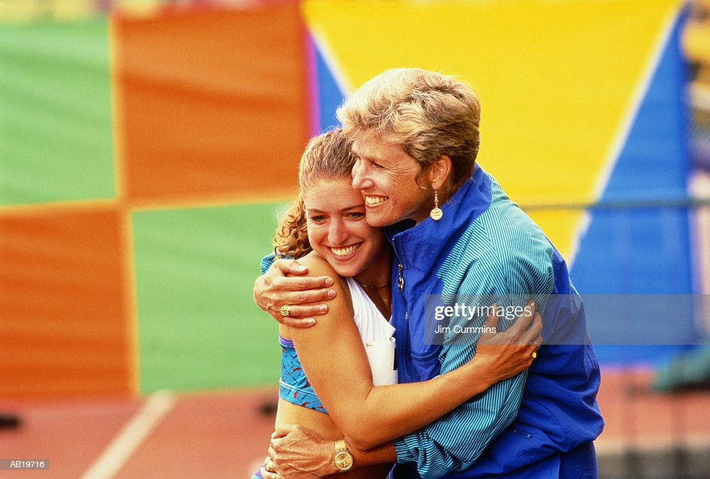 Female coach hugging female athlete at track event, smiling : Stock Photo