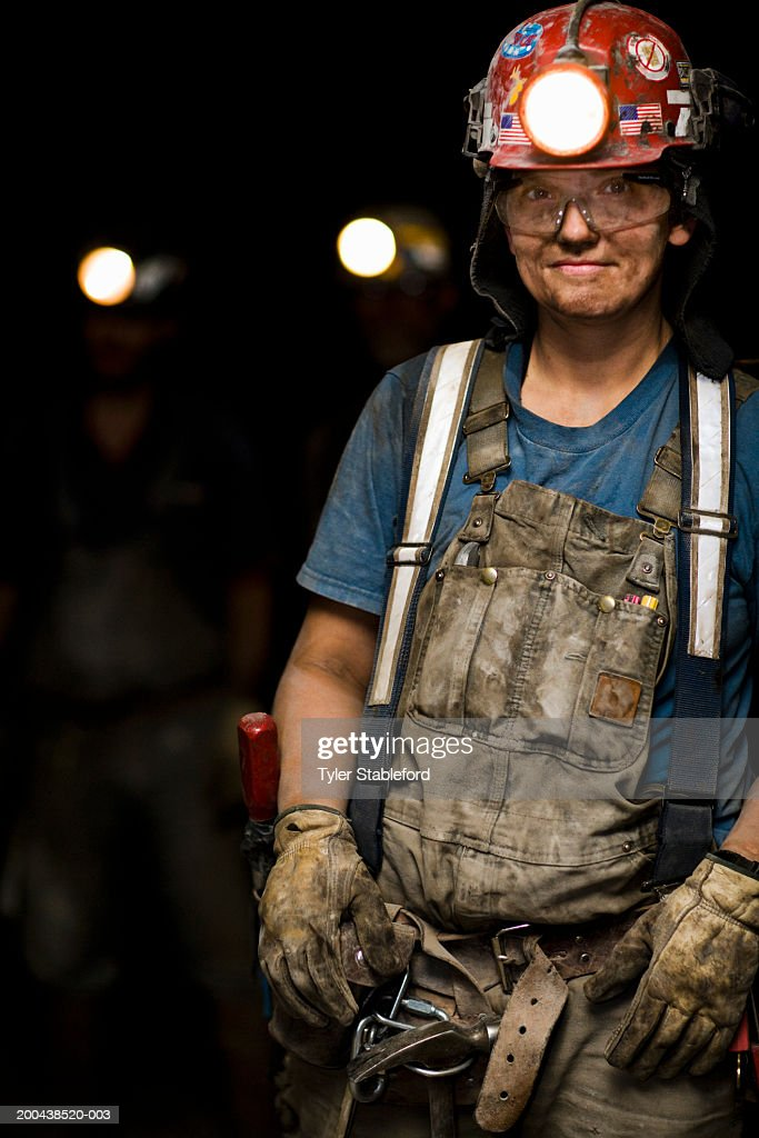 Female coal miner smiling in mine, portrait, close-up : Stock Photo