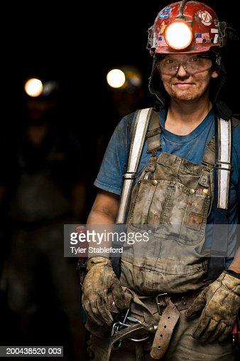 Female coal miner smiling in mine, portrait, close-up : Stock Photo