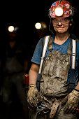 Female coal miner smiling in mine, portrait, close-up