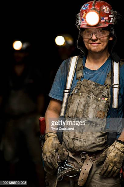 Female coal miner smiling in mine, portrait, close-up