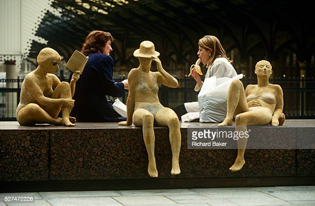 Female colleagues enjoy a chat over an alfresco lunch in the city alongside an art installation of women at the beach Rather suggestively we see one...