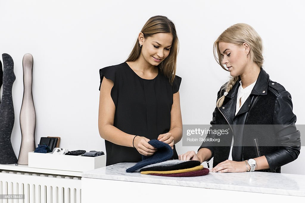 Female colleagues examining beanie hats : Stock Photo