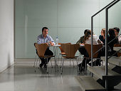 Female colleagues having meeting in board room, man sitting alone