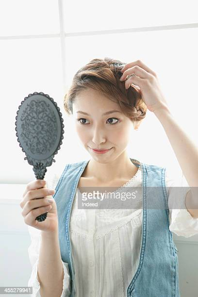 Female college student gazes at a hand mirror by the window