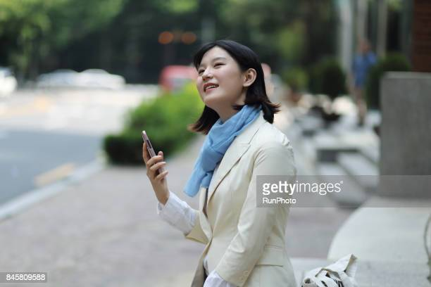 Female college student in alley with smartphone