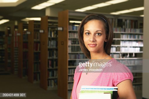 Female college student in library, portrait, close-up : Stock Photo