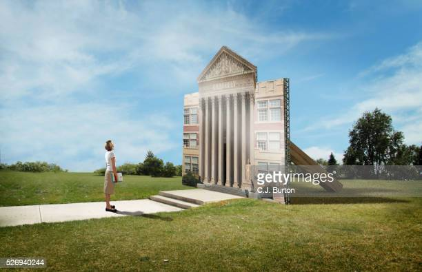 Female college student stands in front of flat facade of college building