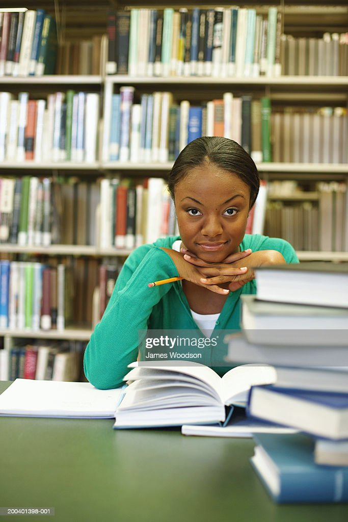 Female college student studying in library, portrait : Stock Photo
