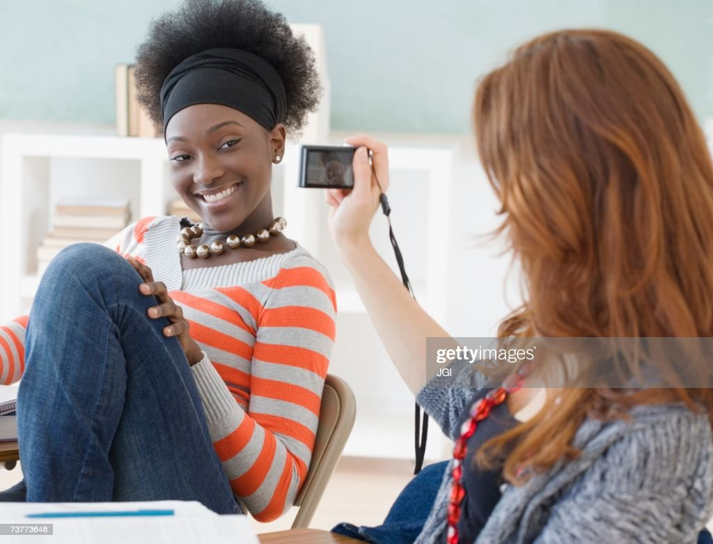 Female college student taking photograph of friend in classroom